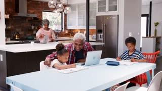 Children Doing Homework In Busy Multi Generation Family Home