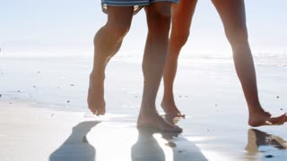 Close Up Of Couples Legs Walking Along Shoreline On Beach Vacation