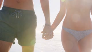 Close Up Of Couples Walking Along Shoreline On Beach Vacation