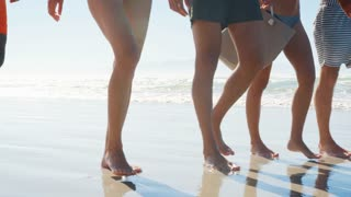 Close Up Of Friends Legs Walking Along Shoreline On Beach Vacation