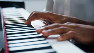 Close Up Of Pupil With Teacher Playing Piano In Music Lesson