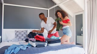 Couple At Home Packing Holiday Suitcase In Bedroom