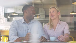 Couple Meeting For Date In Coffee Shop Shot Through Window