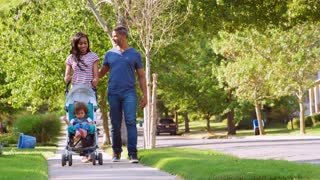 Couple Push Daughter In Stroller As They Walk Along Street