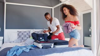 Couple Trying To Close Full Holiday Suitcase In Bedroom