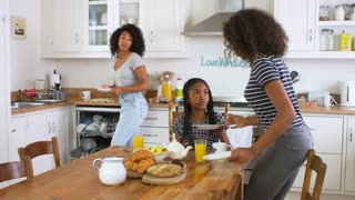 Daughters Helping Mother To Clear Table After Family Breakfast