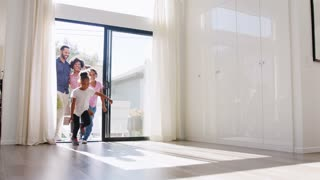 Excited Family Exploring New Home On Moving Day