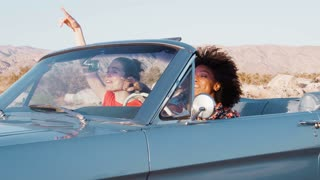 Excited female friends driving convertible car on a highway