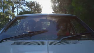 Exterior View Of Friends In Car Enjoying Summer Road Trip