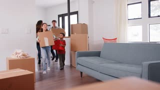 Family Carrying Removal Boxes Into New Home On Moving Day