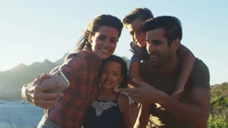 Family Posing For Holiday Selfie On Cliffs By Sea