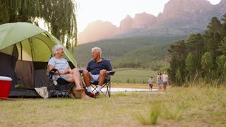 Family returning to grandparents' tent on camping holiday