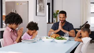 Family Saying Grace Before Meal Around Table At Home