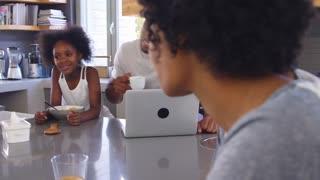 Family Sitting In Kitchen Enjoying Morning Breakfast Together