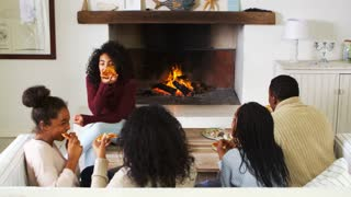 Family Sitting On Sofa In Lounge Next To Open Fire Eating Pizza