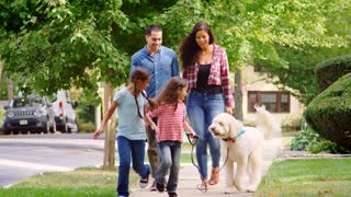 Family Walking Dog Along Suburban Street