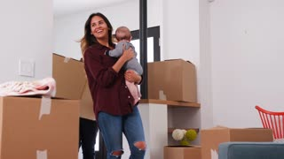 Family With Baby Carrying Removal Boxes Into New Home On Moving Day