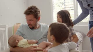 Family With Children And Newborn Son In Nursery