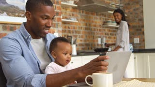 Father And Baby Daughter Use Laptop As Mother Prepares Meal