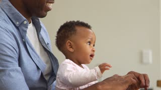 Father And Baby Daughter Using Laptop At Home Together