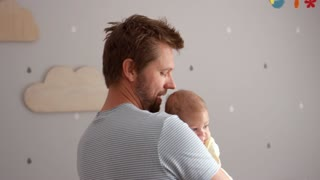 Father Comforting Baby Son In Nursery