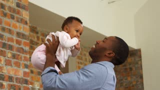 Father Plays Baby Daughter At Home As Mother Watches