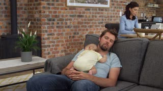Father With Baby Son Sleep On Sofa As Mother Works On Laptop