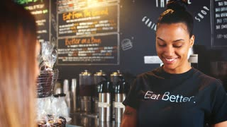 Female Barista Serving Customer With Takeaway Coffee In Cafe