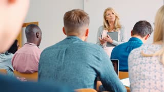 Female College Tutor With Digital Tablet Teaches Mature Students
