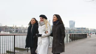 Female Friends Walk Along South Bank On Winter Visit To London