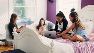 Four teen girls hang out using laptop and phones in bedroom