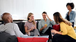 Friends laughing over drinks at a loft apartment, close up