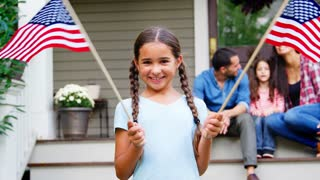 Girl With Family Outside House Holding American Flags