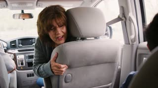 Grandmother turns around to her grandson in the back of car