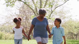 Grandmother Walking In Park And Holding Hands With Grandchildren