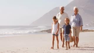 Grandparents And Grandchildren Walking Along Beach Carrying Picnic Basket