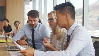 Group Of Businesspeople Meeting Around Table In Boardroom