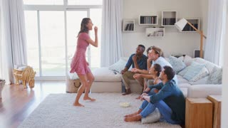 Group Of Friends At Home Having Fun Playing Charades Together