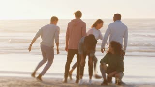 Group Of Friends Having Fun On Winter Beach Together