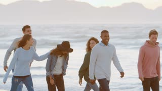Group Of Friends Walking Along Winter Beach Together