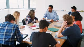 Group Of High School Students With Male Teacher Working At Desk