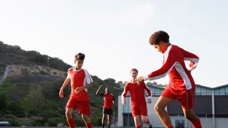 Group Of Male High School Students With Coach Playing In Soccer Team