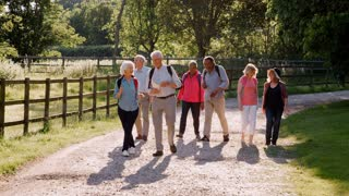 Group Of Senior Friends Hiking In Countryside Together