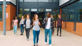 Group Of Students Walking Outside College Buildings