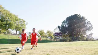 Group Of Young Boys In Soccer Team Kicking Ball Shot In Slow Motion