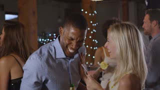 Happy black man and white woman talking at a party, side view, shot on R3D