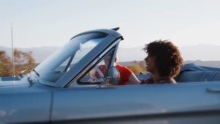 Happy female friends driving in convertible, one raising arm