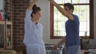 Happy Hispanic couple dancing in kitchen in the morning, shot on R3D
