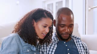 Happy young black couple talking and sitting on sofa