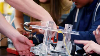High School Pupils Building Robotic Vehicle In Science Lesson Together